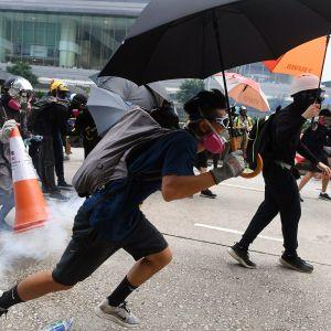 Mustiin pukeutunut mielenosoittaja juoksee kadulla Hongkongissa.