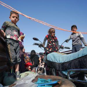 Lapset seisovat avolava-auton lavalla Syyriassa. Auto on matkalla pois taisteluiden alta.