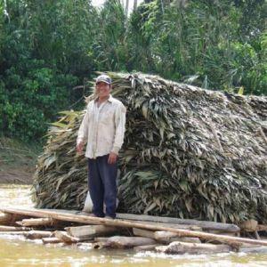 Hymyilevä mies seisoo kelluvalla lautalla, jonka kajuutan katto on katettu palmunlehdillä.