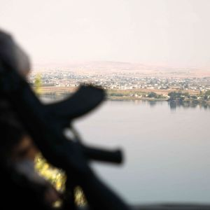 Turkin tukemien syyrialaisjoukkojen taistelija katseli joen toiselle puolelle kurdien hallitsemalle alueelle Awshariyahin kylän lähistöllä Pohjois-Syyriassa. Lauantaina yhteenotoissa kuoli 15 ihmistä sotaa tarkkailevan järjestön mukaan.