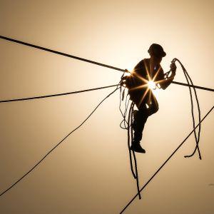 Intialainen mies työskentelee sähkövoimalinjojen parissa.