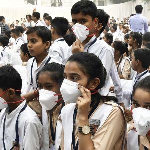 Intialaisia koululaisia hengityssuojaimet kasvoillaan.