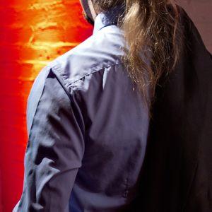 Miehen selkä kuvaajaan päin Sexhibition-messuilla.