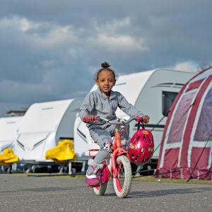 5-vuotias eritrealainen Divora polkee pyörällään matkailuautorivistön ohi. Saksan Frankfurtissa sijaitsevaan Rebstockin puistoon oli sijoitettu hieman yli sata rekisteröityä pakolaista helmikuussa 2016.