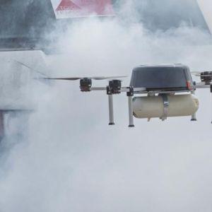 Pelastuslaitoksen drone savupilven keskellä auton edessä.