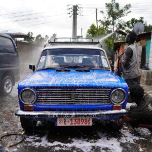 Mies pesee sinistä Ladaa Etiopian pääkaupungissa Addis Abebassa.