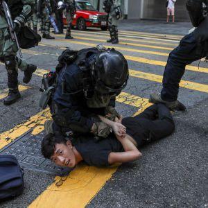 Mellakkapoliisit pidättävät miehen.