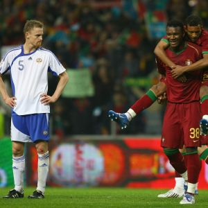 Hannu Tihinen of Finland looks on as Makukula and Jorge Ribeiro of Portugal celebrate qualification