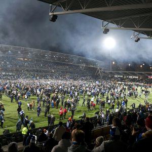 Ihmiset ovat rynnänneet kentälle pelin päätyttyä.