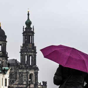Nainen suojautuu sateelta Dresdenissä.