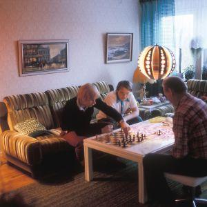 Ruotsinsuomalaiset pelaavat shakkia kotona.