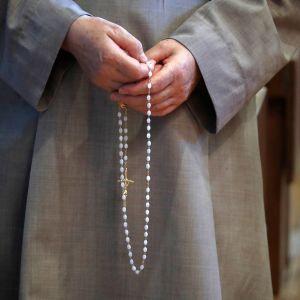 Rukoileva nunna rukousnauha kädessään.