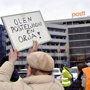 Posti ja logistiikka-alan unioni PAU järjesti mielenosoituksen Postin työehtojen romuttamista vastaan Postin pääkonttorilla Helsingin Ilmalassa 12. marraskuuta.