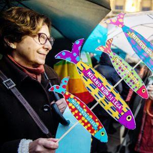 Nainen kantaa sardiinin muotoisia kylttejä mielenosoituksessa Milanossa.