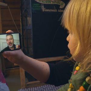 Nainen ja pikkupoika katsovat älykännykän kuvaa.
