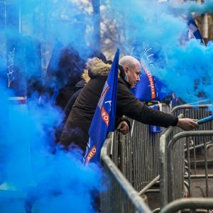 Mielenosoittaja sinistä savua levittävä soihtu kädessään.