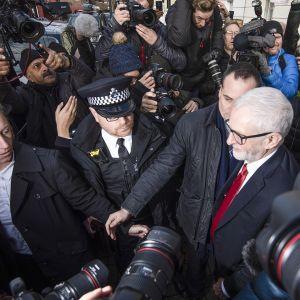 Britannian työväenpuolueen puheenjohtaja Jeremy Corbyn median piirittämänä lähtiessään kotoaan tappion jälkeen 13. joulukuuta.