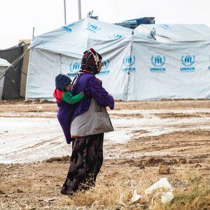 Nainen kantaa lasta selässään al-Holin leirillä.