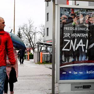 Mies kävelee kadulla Zagrebissa Kolinda Grabar-Kitarovicin vaalijulistetta julistetta katsellen.