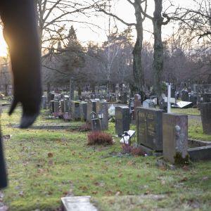 Mies on hautausmaalla ja katselee hautakiviä. Hän seisoo kuvan vasemmassa laidassa ja hänestä näkyy vain osa vartaloa ja oikea käsi. Laskeva talvinen aurinko pilkottaa käden kainalosta.