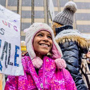 Tummaihoinen lapsi hymyilee lumisateessa. Hänen vieressään on kyltti, jossa todetaan tulevaisuuden olevan naisten.
