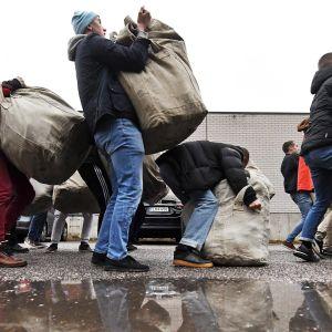 Alokkaat kantavat varusteitaan säkeissä.