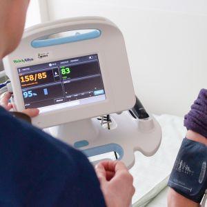 Sairaanhoitaja mittaa potilaan verenpainetta