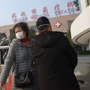 Terveysasema Wuhanissa ja hengityssuojaimella varustettu nainen