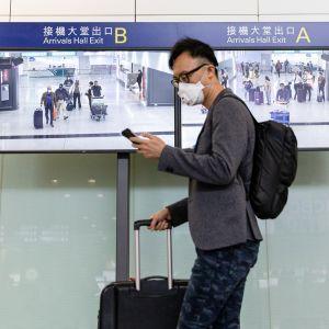 Hongkongiin saapuvalla matkustajalla hengityssuojain naamalla.