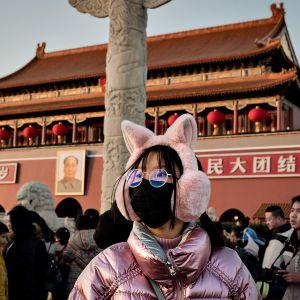 Nuorella naisella on valkoinen suojamaski kasvojensa edessä Taivaallisen rauhan aukiolla Pekingissä 23. tammikuuta 2020.