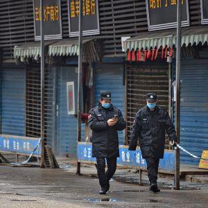 Vartijoita Wuhanin kaupungissa sijaitsevan Huananin ruokatorin ulkopuolella 24. tammikuuta 2020.