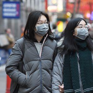 Ihmiset yrittävät estää tautitartunnat kasvomaskeilla.