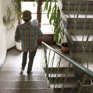 Mies kantaa vauvaa sylissään rappukäytävässä.