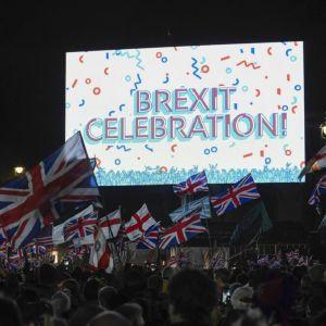 """Kuvassa kyltti, jossa lukee """"Brexit Celebration"""". Sen edessä on Britannian lippuja."""