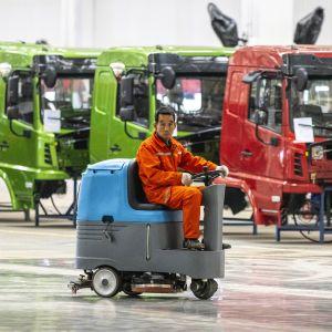 Mies ajaa siivouskoneella autotehtaassa Kiinassa.