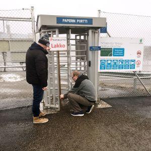 Kaksi miestä poistavat Paperiliiton lakkokylttiä UPM:n Kymin paperitehtaan portilta Kouvolassa.