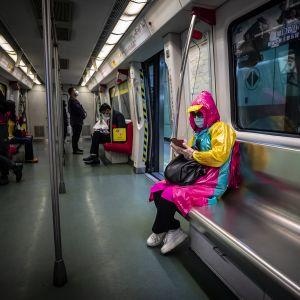 Nainen hengitysmaskin kanssa Guangzhoun metrossa Kiinassa.