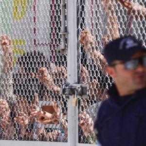 Turvapaikanhakijat ja siirtolaiset seisovat verkkoaidan takana. Oikeassa reunassa seisoo lippalakkipäinen univormupukuinen mies ja katselee oikealle.