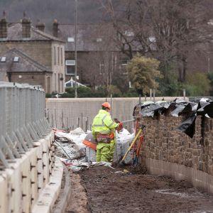 Rakennusmiehet rakentavat tulvaesteitä Mytholmroydissa.