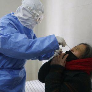 Lääkäri ottaa virustestin kuumeiselta potilaalta Kiinassa.