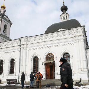 Toimittajia ja miliisi Nikolauksen kirkon edustalla Moskovassa.
