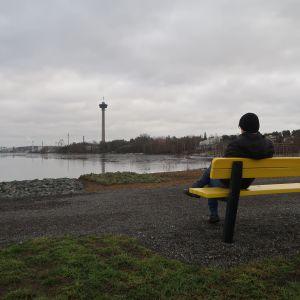 Mies istuu puiston penkillä Näsijärven rannalla