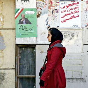 Iranilainen nainen kävelee kadunvierellä olevien vaalimainosten ohi Teheranissa 12. helmikuuta 2020.