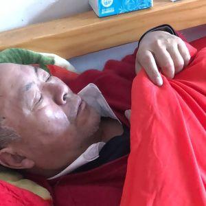Kiinalainen mies makaa sängyssä kuumeisena.