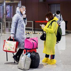Matkustajia Daxingin lentokentällä Pekingissä 14. helmikuuta.