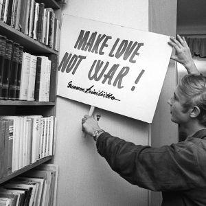"""Erkki Tuomioja kädessään Teiniliiton banderolli """"make love not war"""" 1968."""