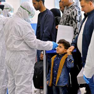 Iranista saapuvalta lapselta mitataan lämpötila Najafin kansainvälisellä lentoasemalla Irakissa.