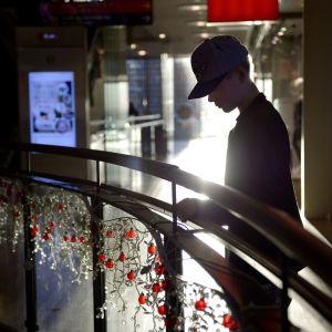 Nuori poika yksinään  kauppakeskuksessa.