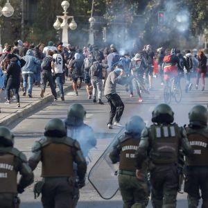 Poliiseja ja mielenosittajia.