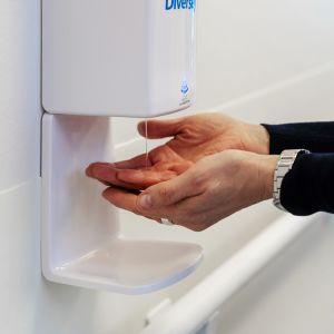 Henkilö ottaa käsidesiä automaatista.